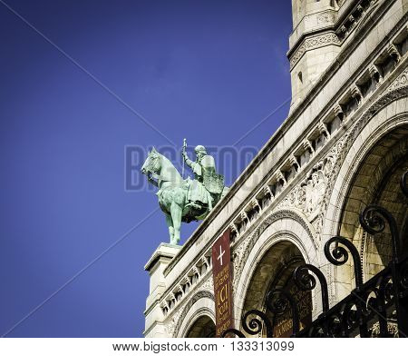 PARIS, FRANCE - MAY 17, 2016: Equestrian bronzed statue of Jeanne D'Arc holding a sword over the entrance to Basilica du Sacre-Coeur, Paris