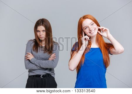 Portrait of two cheerful and unhappy young women over white background