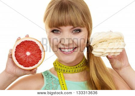 Woman with measuring tape holds in hands cake and grapefruit choosing deciding between sweet food or fresh fruit make dietary choice. Weight loss diet dilemma concept. Isolated on white