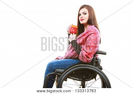 Real people disability and handicap concept. Teen girl unrecognizable person sitting on wheelchair holding tea mug studio shot on white