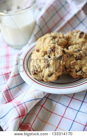 Chocolate and butterscotch chip cookies on a colorful dish with glass of milk on multi-colored dish cloth