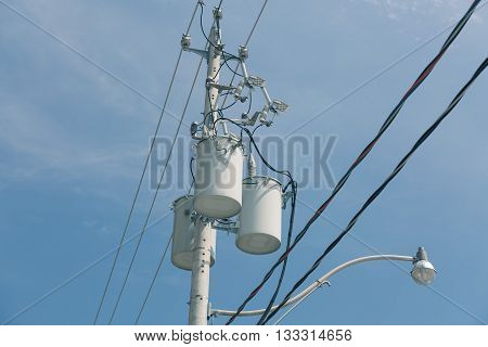 Old style electrical transformers hanging on light pole against dark blue sky