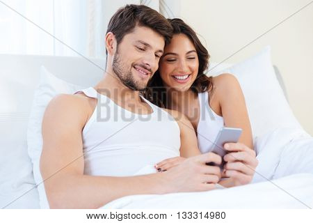 Young sweet couple in bed looking at a mobile phone at home