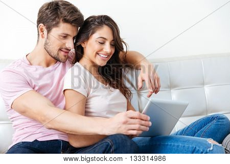 Happy young couple sitting on couch using a tablet computer isolated on white background
