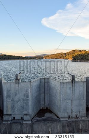 Weighted flood gates on Jindabyne Dam, confining the Snowy River.  The surrounding mountain landscape and cloudscape.  Lake Jindabyne is part of the ground breaking 'Snowy Mountains Hydro-Electric Scheme' diverting water from the Snowy River to the west o
