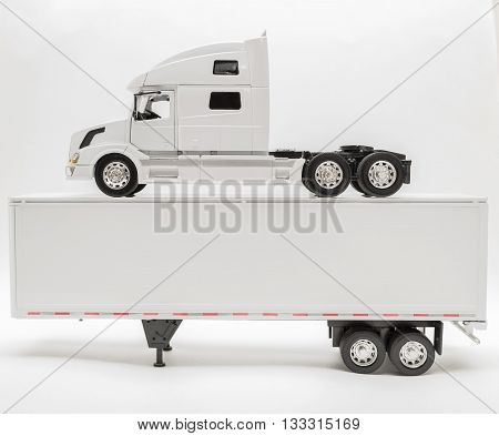 Closeup view of transport truck standing on top of the trailer isolated on white, grayish background