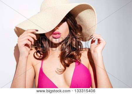 Close-up portrait of an attractive young sexy woman in beach hat isolated on the white background