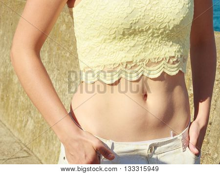 Closeup of sexy alluring woman hips and belly. Slim girl wearing white shorts lace shirt outdoor. Summer fashion