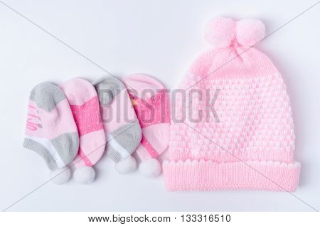 Pastel socks and hat for new born baby on white background