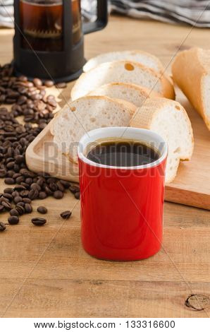 Americano In Red Cup With Coffee Beans On Wooden Background