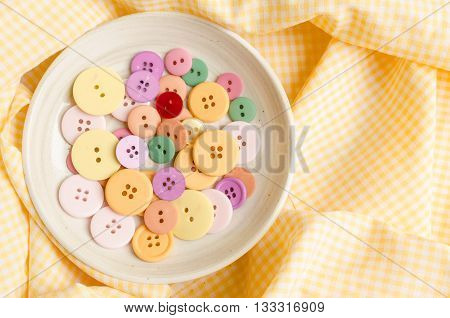 Colorful cloth buttons on yellow tablecloth background