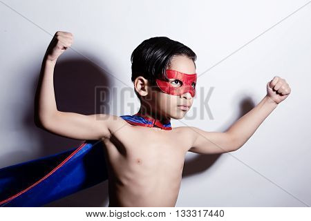 Super Strength.  Adorable, mixed race boy, wearing a cape and mask and showing off his muscles.
