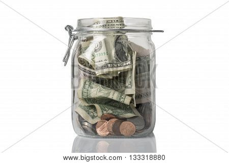 A tip jar or savings jar filled with American coins and bills.