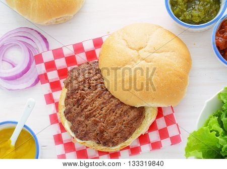 Grilled beef hamburger with condiments in horizontal format is traditional summer fare