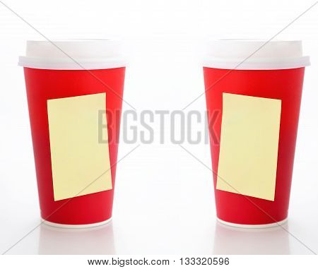 Coffee to go. Two paper coffee cups with blank yellow sticky notes