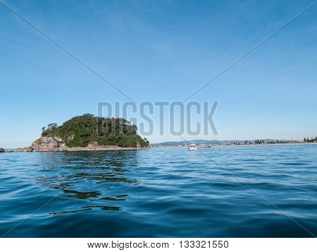 small off-shore island across blue of ocean from low point of view with Mount Maunganui beach bakhground.