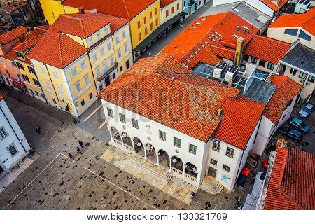 Central square of coastal town Koper in Slovenia seen from above. Historical buildings with red roofs, cafes, shops and restaurants
