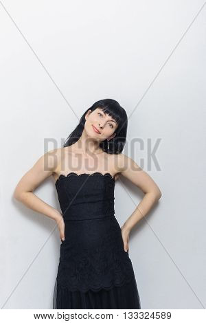 Beautiful young model woman in black lace dress posing over white background