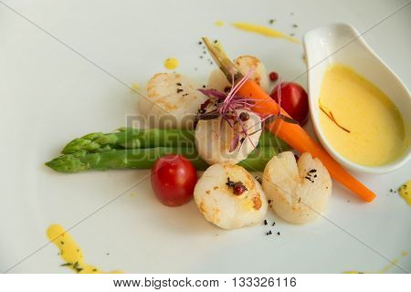 A gourmet seared scallops with garnishes and sauce