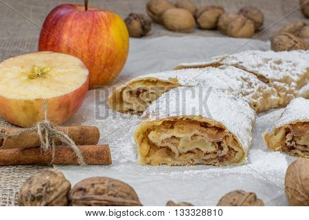 Detail On A One Slice Sugared Homemade Apple Strudel On A Baking Paper