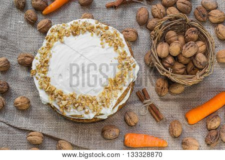 Top View On Carrot And Walnut Cake Topped With Cream  On Jute Background