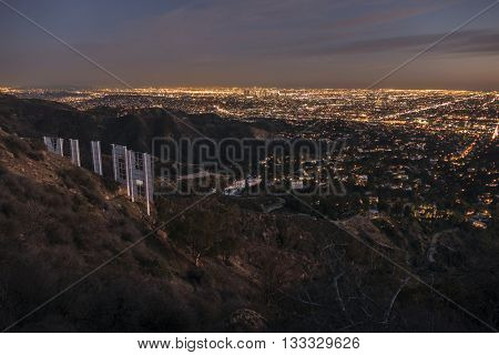Los Angeles, California, USA - February 4, 2016:  Hollywood sign and downtown Los Angeles hilltop cityscape dusk view.