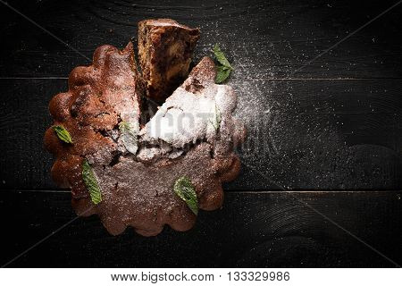 Chocolate cake with cherry on a black table (top view)