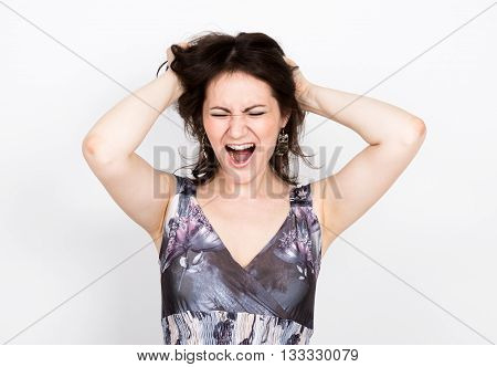 beautiful young brunette woman in a colorful dress posing and expresses different emotions. woman's hands shows various signs, tearing his hair. close-up portret.