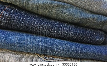 Stack of folded blue denim jeans in a full frame horizontal stripe pattern, blurry denim background photo.