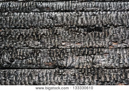 Burnt wooden wall of house background texture