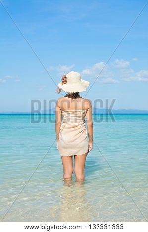 Woman Looking Out To Sea From Tropical Beach With Sarong And Summer Hat.