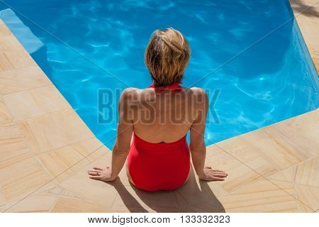 Lady in Red swimming costume relaxing by the pool