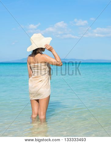 Asian Woman On Tropical Beach Wearing Sarong And Summer Hat.