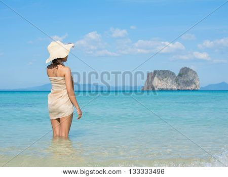 Asian Woman Wearing Summer Hat And Sarong On A Tropical Beach Looking Out To A Distant Island.