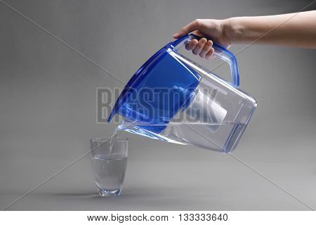 A hand pouring filtered water in the glass, on the grey background