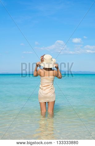 Woman Wearing Sarong And Summer Hat Looking Out To Sea From Idyllic Tropical Beach.