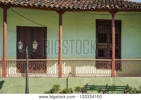 porch of green tropical House with tiled roof and shutters on the window