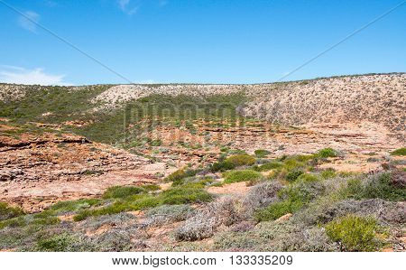 Rugged scenic landscape at Pot Alley gorge with red sandstone rock and native green plants under blue skies in Kalbarri, Western Australia.
