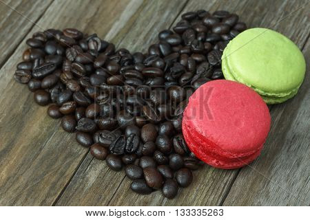 Macaroon dessert and coffee beans arranged in a heart shape on the wooden floor.
