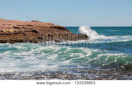 Turquoise Indian Ocean seascape with waves crashing the sandstone rock outcropping at the secluded cove at Pot Alley under clear blue skies in Kalbarri, Western Australia.