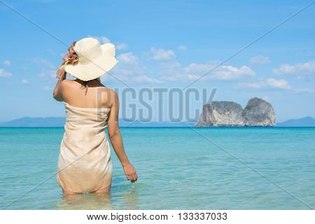 Woman Wearing Sarong On Tropical Beach Looking Out To Sea.