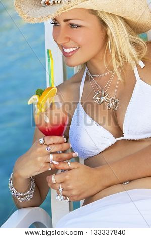 Stunningly beautiful young blond woman in straw cowboy hat and white bikini enjoying a cocktail by a turquoise blue sea
