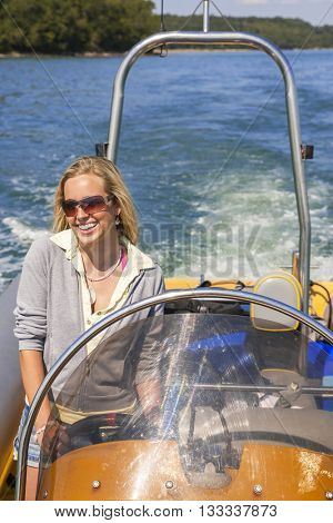 Beautiful happy young blond woman or girl having fun driving a power boat or rib at sea around a coast line