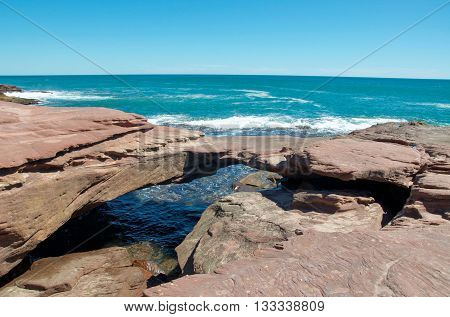 Natural sandstone bridge formation connecting the coastal outcroppings at Pot Alley gorge on the Indian Ocean coast line in Kalbarri, Western Australia.