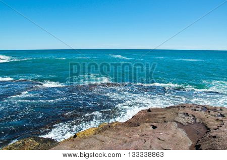 Tranquil Indian Ocean seascape with waves rolling into sandstone outcroppings at Pot Alley on a clear day in Kalbarri, Western Australia.