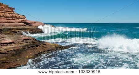 Indian Ocean waves crashing into the sandstone cliff outcroppings at Pot Alley on a clear day in Kalbarri, Western Australia.