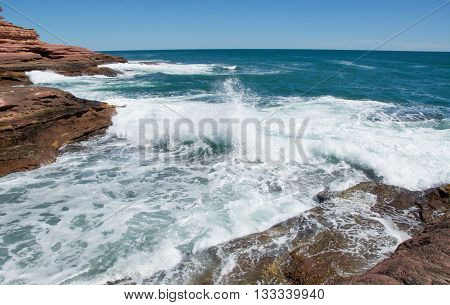 Turquoise Indian Ocean waves rushing the coastal sandstone recess with layered cliffs at Pot Alley under clear blue skies in Kalbarri, Western Australia.