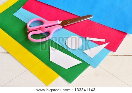 Scissors, set of colored paper, paper patterns. Shapes cut from colored paper. Elements for creating postcard. Children entertainment. Art lesson and activity for children. Developing motor skills