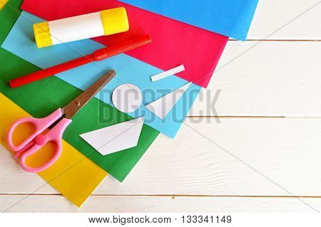 Glue stick, scissors, red marker, colored sheets, paper patterns. Set to create original summer card. Patterns for card making. Stationery. Toddler and preschool art lesson. Wooden background