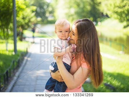 Youmg happy woman playing with her cute baby in summer sunny park outdoor.